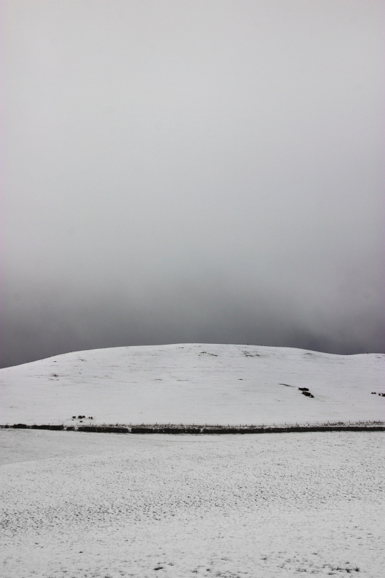 photo of a snowy hill with brooding clouds behind it
